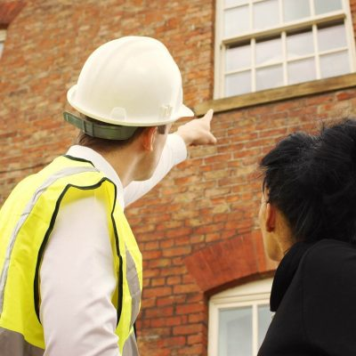 man in a hard hat with a woman looking at a brick building